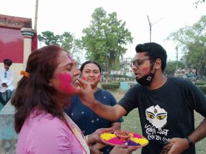 This photograph shows three participants in the Dol Jatra event applying 'abir' to each other. To the left is Mousumi Guruma holding a plate full of 'abir' in different colours. She's smiling with her eyes closed as a bespectacled male participant (to the right of the photograph) applies some colour to her face. The male participant also has some colour on his face. A third participant, a woman, facing the camera, is standing next to the other two; she smiles and looks on. She too has spots of colour on her face. In the background, some tall trees of the Kalyani Central Park and a few buildings beyond the park are visible. Photo courtesy Nadia Ranaghat Sampriti Society