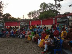 This is a near dusk-time long shot of the audience for the Dol Jatra event. There are around 70-80 people, seated in an amphitheatre arrangement in the Kalyani Central Park. The audience is seated in three rows gracefully arching away from the camera, with each row on a higher ground than the one in the front. The audience includes some of the event performers and is a colourful lot in terms of the apparel worn. Some audience members are busy peering at their mobile phones while the others are watching the happenings on the stage (not in the picture). Behind the last row is a line of round columns. The space between some of the columns is screened with red and yellow cloth. Where the cloth is missing, buildings beyond the park are visible. The sky above is bright though the sun is already setting. Tall trees frame the background of the photograph. Photo courtesy Nadia Ranaghat Sampriti Society