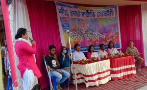 """In this daytime medium-shot photograph, Argha Ray Chowdhuri, aka Silk, Secretary, Nadia Ranaghat Sampriti Society welcomes and thanks the speakers for the Dol Jatra event, seven of them, seated in a row on a small open air stage. Silk speaks into a microphone, facing the speakers who are seated behind two long tables covered with red and yellow drapes. The tables have small bouquets of flowers gifted to the speakers and small bottles of drinking water placed on them. Behind the speakers is a wall of long curtains in deep pink and white. A narrow roof has been created above the speakers with the same cloth as the curtains. A colourful event banner is pinned on to the curtains behind the speakers. The banner carries the name and logo of Nadia Ranaghat Sampriti Society and has """"Basanta Utsav"""" written across the centre in large Bengali letters. The background of the banner is a mishmash of Dol Jatra colours. The banner carries also the event date, time and venue details. Photo credit: Rafiquel Haque Dowjah"""