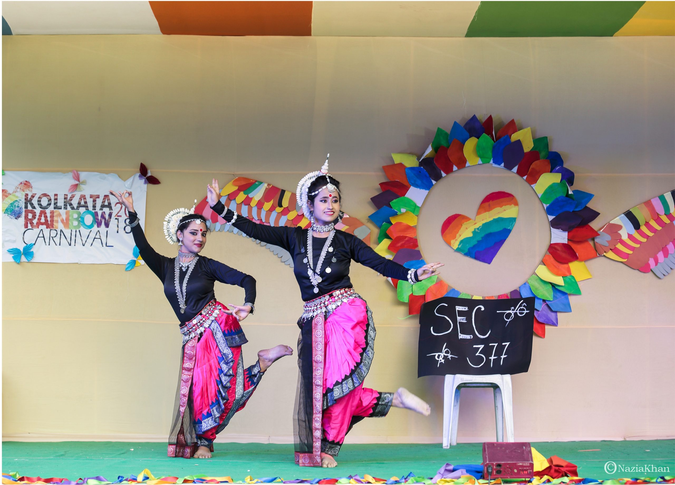 "This photograph shows a classical dance performance in progress on a stage at the 'Kolkata Rainbow Carnival 2018'. Two female dancers are caught on camera executing an intricate move and 'mudra'. Just next to them, to their left is a placard placed on a chair – the placard says ""Sec 377"", with the symbols of two same-sex couples (a male and female couple each) crossed out. This implies that the existence of a law like Section 377 of the Indian Penal Code stigmatizes and criminalizes same-sex sexual and / or romantic relationships. Behind the dancers, to their right, pasted on the back wall of the stage is a colourful poster with butterfly cut-outs pinned on it – the poster says ""Kolkata Rainbow Carnival 2018"". Large rainbow themed decorations cover the rest of the back wall. The carnival was organized by the West Bengal Forum for Gender and Sexual Minority Rights on February 18, 2018 at Triangular Park in South Kolkata. Photo credit: Nazia Khan"