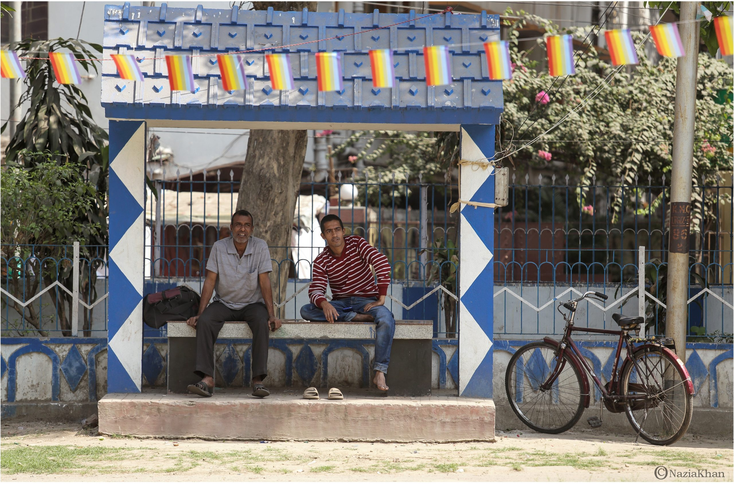 In this long shot photograph one can see the mood on the sidelines of the 'Kolkata Rainbow Carnival 2018'. Two men, one middle aged and the other younger, are seated on a stone bench on a raised platform under a blue and white shelter. Both the men seem to be gazing at the happenings of the carnival, and are smiling at what they see. The older man is dressed in t-shirt and trousers, while the younger man is in a light pullover and jeans. The older man has a shoulder bag kept next to him on the bench. From the looks of it, both men seem to be labourers. A bicycle is parked next to the shelter and behind it is a lamp post. The shelter is at one of the boundaries of the park. Behind the shelter one can see the boundary railing, and behind it a house and several shrubs and flowering plants (including a bougainvillea tree). In the foreground one can see a string of rainbow flags cutting across the entire width of the photograph. The carnival was organized by the West Bengal Forum for Gender and Sexual Minority Rights on February 18, 2018 at Triangular Park in South Kolkata. Photo credit: Nazia Khan