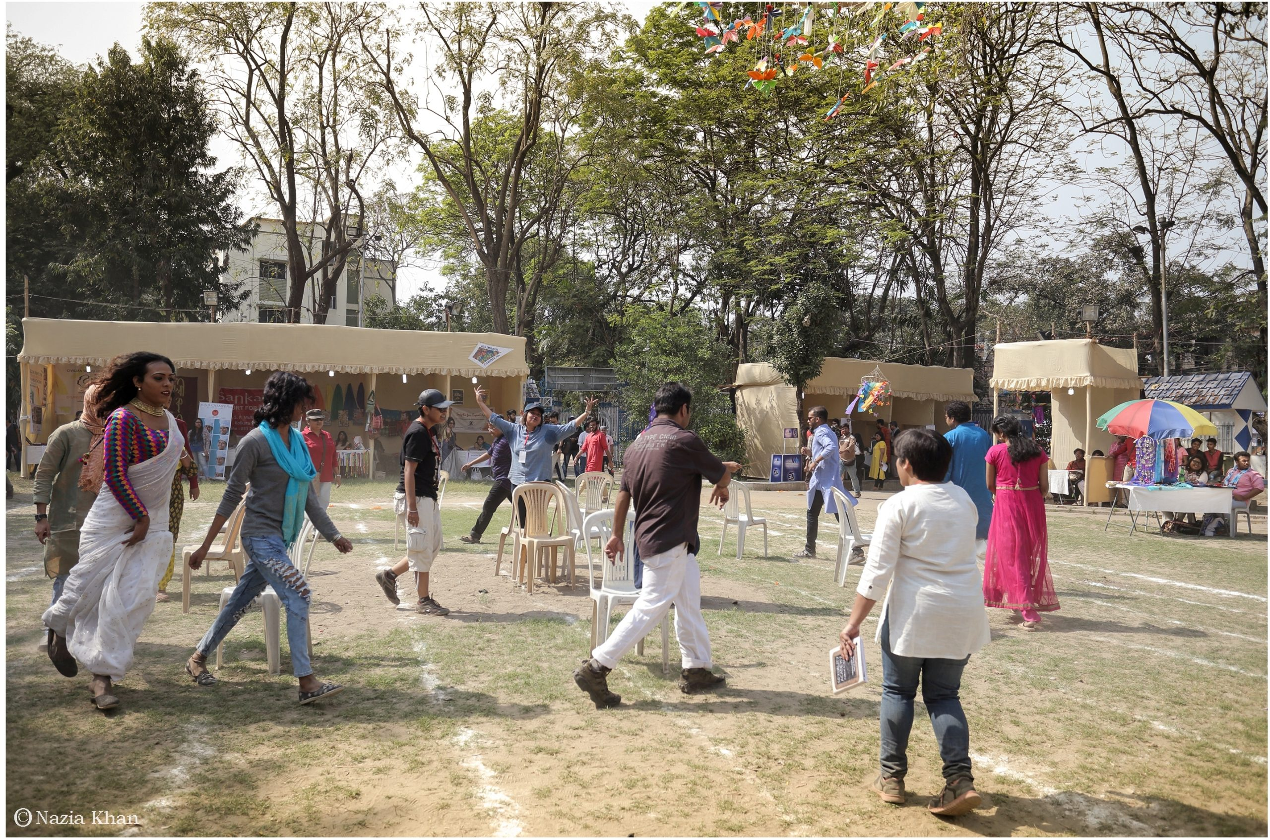 This photograph shows a long shot of a game of musical chairs in progress under the bright sunlight at the 'Kolkata Rainbow Carnival 2018'. Apart from 9-10 players doing the rounds around eight chairs, three umpires can be seen engaged in the game. The game is being played at the centre of the park, which is the venue of the carnival. The playground has light grass and is marked with white chalk lines meant for races and other carnival games. In the background are a number of stalls with displays of decoration, craftwork and clothes. The stalls have a few visitors. The camera also takes in tall trees behind the stalls ringing the park. A building adjacent to the park is visible through the trees. The carnival was organized by the West Bengal Forum for Gender and Sexual Minority Rights on February 18, 2018 at Triangular Park in South Kolkata. Photo credit: Nazia Khan