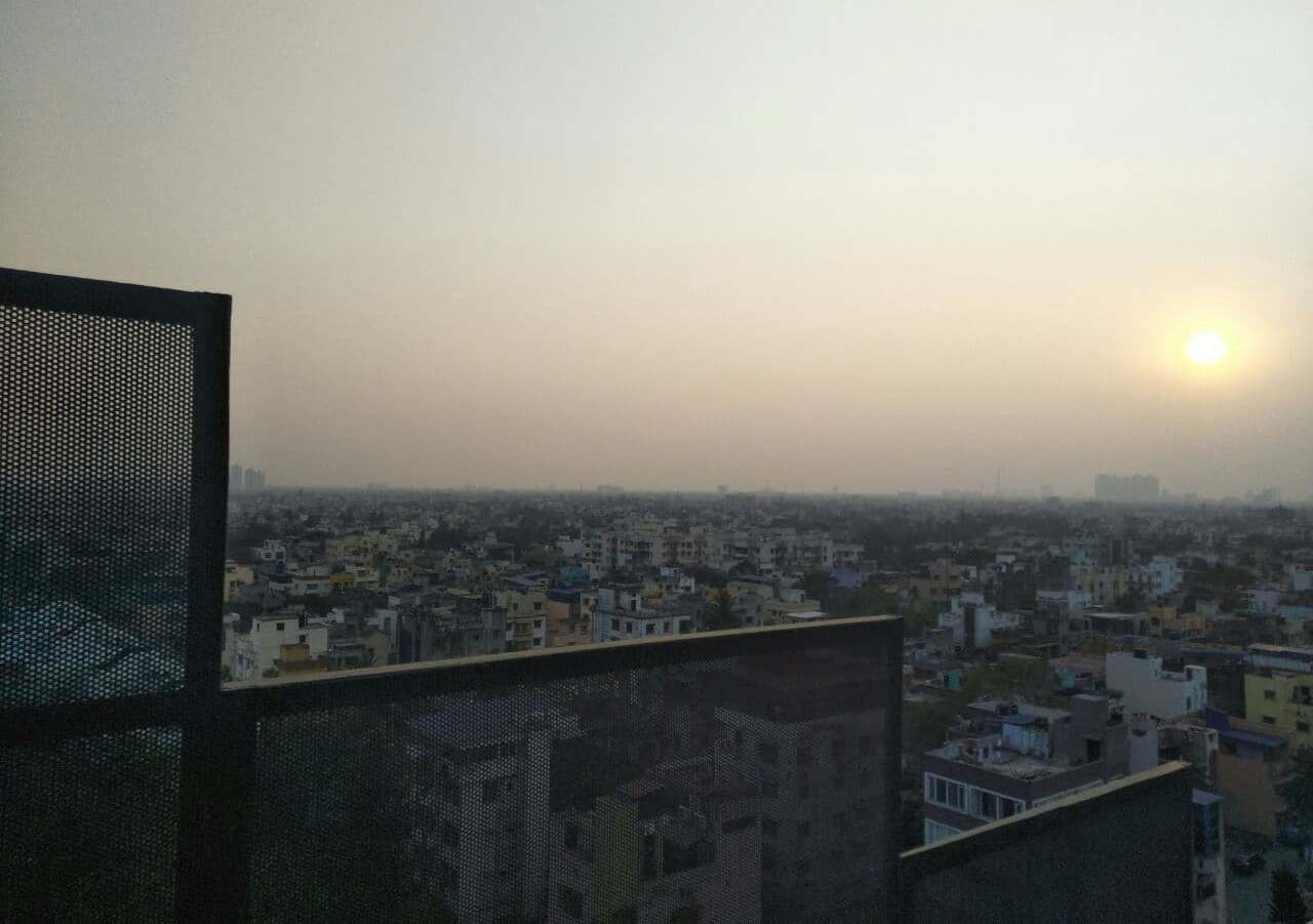 This photograph is symbolic of the subject matter of the article. It shows a somewhat dispiriting aerial view of Kolkata city at dusk time. The photograph has been taken from the rooftop of a city high rise. The right hand side of the photograph has the setting sun, and the sky is filled with an overpowering haze of dust. The sprawling city below is a mix of buildings, some of them high-rises in the horizon, and some trees as well, but there is little to cheer about the scene. In the forefront, from the point where the photograph was shot, is a rooftop security rail made of a steel netlike structure that cuts through the left and lower parts of the photograph. The security rail seems to jag through the photograph, creating an impression of dissonance. Photo credit: Pawan Dhall
