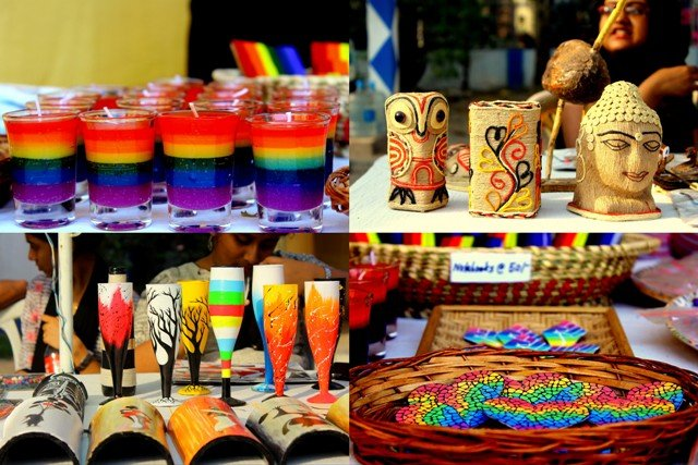 This photograph is made up of four smaller panels of equal dimensions. Each panel shows a display of handicrafts at the carnival. Clockwise from top left: An array of rainbow coloured wax candles in glass containers; figurines of an owl and Lord Buddha and a pen holder made up of jute fibre and thread work in different colours; heart shaped badges with a mosaic pattern and rainbow shades lying in a wicker basket; and a row of cocktail glasses painted in a variety of patterns and motifs. Photo credit: Prosenjit Pal