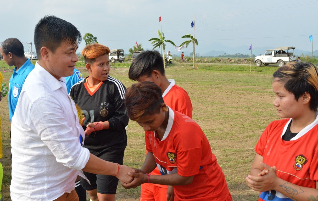This second photograph shows MLA Heikham Dingo (from Sekmai constituency), Parliamentary Secretary, Department of Rural Development and Panchayati Raj, Government of Manipur greeting the two teams ETA and Women Football Association during the inauguration of their exhibition match. In the picture he can be seen shaking hands with a player of the Women Football Association. Other players and referees can also be seen lined up. The match was played in a village ground near Imphal city, and in the background there are a few trees along a lane next to the playground. In the distance are fields and hills. Two army jeeps can also be seen parked on the lane, even as a few villagers pass by. Photo credit: ETA