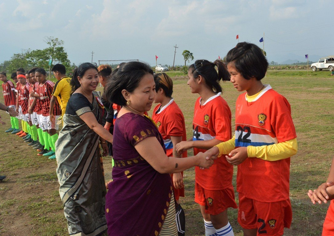 This third photograph shows Randhoni Lairikyengbam from NGO SAATHII and freelance journalist and gender rights activist Thingnam Anjulika Samom greeting the players from the ETA and Women Football Association teams during the inauguration of their exhibition match. In the foreground Thingnam Anjulika Samom can be seen shaking hands with players of Women Football Association, while Randhoni Lairikyengbam follows. The ETA players are in the background. Photo credit: ETA
