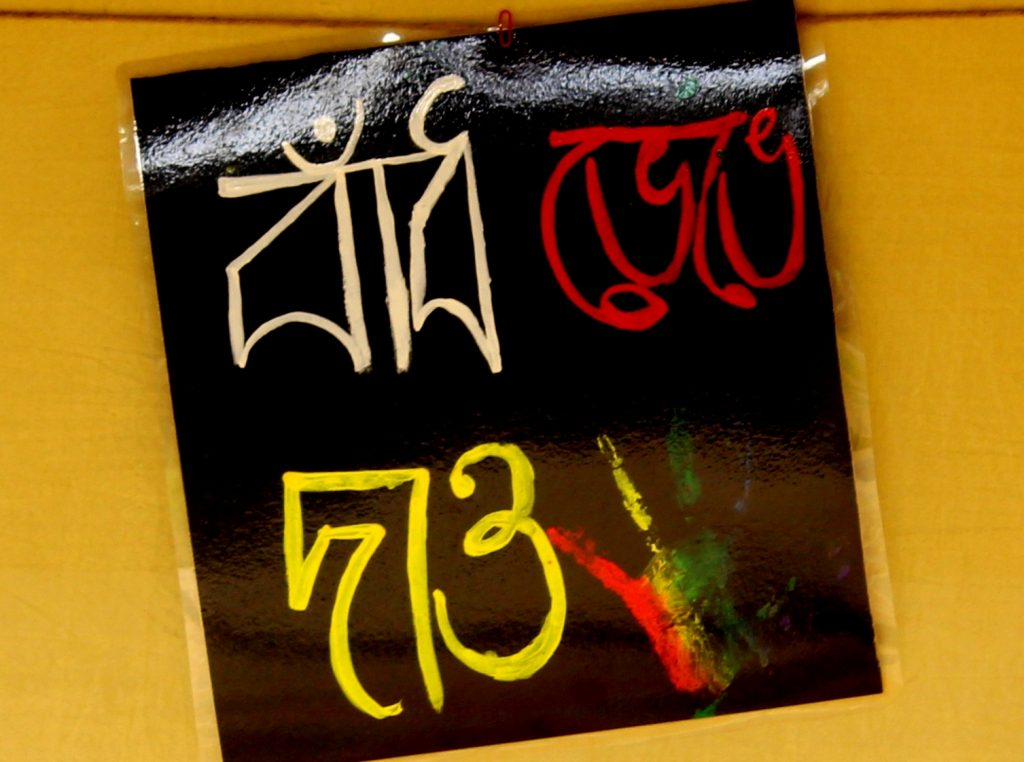 """This photograph shows a poster on display at the 'Kolkata Rainbow Carnival 2018'. It simply says """"Baandh Bhenge Dao"""", a line borrowed from a Bengali song written by Rabindranath Tagore. Translated, it means 'shatter the barrier'. The lettering of the poster is in white, red and yellow on a black background. There is an imprint of a hand painted in red, yellow and green next to the text. The poster has a shiny laminated surface. Photo credit: Prosenjit Pal"""