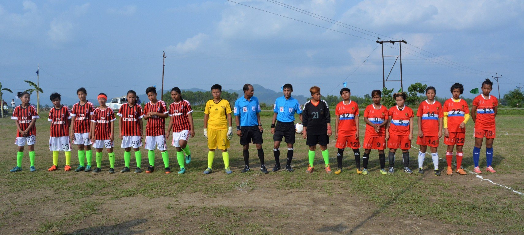 This fourth photograph shows all the players of the two teams ETA and Women Football Association lined up at the start of the match. The ETA players are dressed in maroon and black striped t-shirts, white shorts and light green socks, while their opponents are in a bright orange combination. The ETA goalie is in an all-yellow dress, while Women Football Association's goalie is in an all-black one. In the centre are the two referees (in blue t-shirts and black shorts). To their right are the ETA team and the Women Football Association are on the other side. The ETA t-shirts carry the logo of Emirates, the team's sponsors. The background is an idyllic countryside with trees, hills and an open blue sky, marred only slightly by overhead power lines. A handful of spectators and soldiers can also be seen on the sidelines of the play ground. Photo credit: ETA