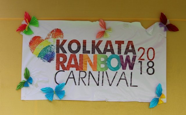 """This photograph shows the main signage of the 'Kolkata Rainbow Carnival 2018' – a colourful poster with a rainbow coloured heart sign and butterfly cut-outs pinned on the margins. The poster says """"Kolkata Rainbow Carnival 2018"""". The writing and the graphics are done on white chart paper. The poster is pasted on to the back wall of a performance stage for the carnival. The back wall is made of mustard coloured fabric. Photo credit: Prosenjit Pal"""