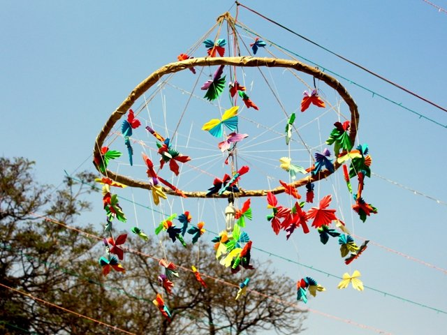 The photograph shows an example of innovative decor at the 'Kolkata Rainbow Carnival 2018'. Numerous colourful butterfly cut-outs pinned on to threads hang from a large hoop-like ring made of a light material. The hoop itself is suspended in mid-air from an overhead plastic wire such that it is parallel to the ground – thick threads tied at several equi-distant points on the perimeter of the hoop bunch together in a common knot on the overhead plastic wire. More threads criss-cross from the perimeter and form a mesh supporting each other. Butterfly cut-outs hang from these threads as well. Several of the threads meet at the centre of the hoop, and a small fluorescent bulb connected to a wire hangs from the centre. This is a day time shot with the entire arrangement looking bright and cheerful against a blue sky. Part of the photograph frame to the left corner is taken over by the branches of several trees in the background. Photo credit: Prosenjit Pal