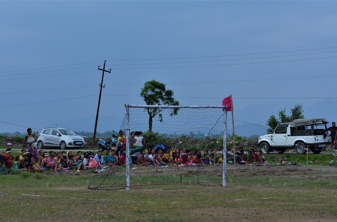 This fifth photograph shows about 50 spectators, all women and girls across different age groups, seated or standing and chatting behind one of the goal nets on one side of the play ground. This makes for a colourful sight set against a bluish sky and the green of the trees and shrubs. A car can be seen parked on a lane close behind the spectators, as also an army jeep. A couple of scooters and bicycles that presumably belong to the spectators can also be seen. An overhead power line looms up next to one of the parked cars. Photo credit: ETA