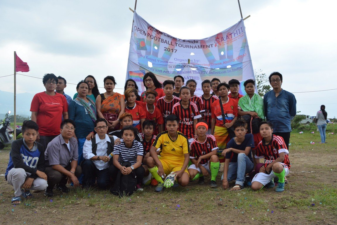 This seventh photograph shows the victorious ETA team along with several well-wishers and ETA group members after the exhibition match. Around 30 people (among them a few queer activists from Manipur) can be seen in the photograph, with the author of this article Oinam Hemabati seated third from left in the front row. The tournament banner with 'Village Level 7-A-Side Open Football Tournament 2017' emblazoned on it rises high above behind them. The names of all co-organizers are also mentioned on the banner, which is hoisted on a frame made of bamboo poles. The banner juxtaposed against a cloudy sky looks majestic. Photo credit: ETA