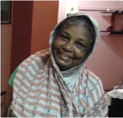 This is an indoor medium shot of Lakhi Bibi standing inside the living room of the author's home. She wears a cheerful smile as she looks at the camera, her head inclined slightly to her left. She is dressed in a patterned light brown and white cotton saree. One edge of the saree covers grey-specked hair on her head. In the background a wall of the living room and a few household objects can be seen. Lakhi's smiling charm is the centre point of the photograph. Photo credit: Pawan Dhall