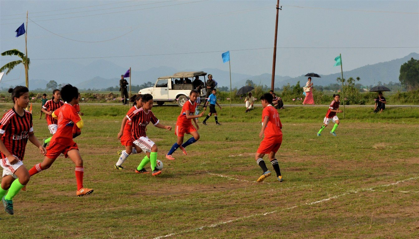 This main photograph shows an exhibition match that was played between the Empowering Trans Ability (ETA) and Women Football Association teams in Manipur earlier these summers (year 2017). The match, played in a village ground near Imphal, was part of the 'Village Level 7-A-Side Open Football Tournament' organized every year by ETA. This match was the only one played in the women's leg of the tournament. The photograph shows an ETA player dribbling and moving ahead with the ball near the opponent team's 'D' area and penalty box. The player is being shadowed by a rival team member, while another rival tries to block their way. There are six other players from both teams in the vicinity. A line referee can be seen in the background, as also a few spectators (some with umbrellas) seated on the sidelines or walking on a lane next to the play ground. A few soldiers seated in an army jeep or standing next to it – an omnipresent sight in Manipur – are among the spectators. The sidelines are marked by small coloured flags hoisted on bamboo poles. In the distant background are fields, trees and hills merging into a grey-blue sky. ETA's players are dressed in maroon and black striped t-shirts, white shorts and light green socks, while their opponents are in an orange combination. ETA, a queer support forum, aims to empower lesbians, bisexual women and trans men in Manipur through football tournaments like these. Photo credit: ETA