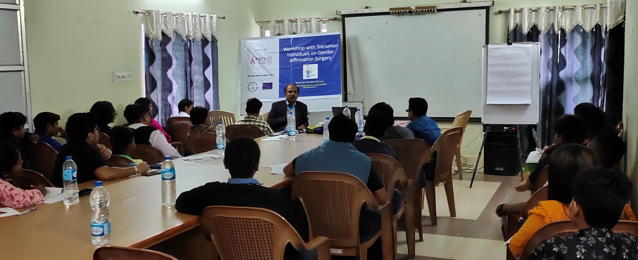 """This photograph shows a workshop on gender affirmative surgery in progress with trans masculine individuals and their allies in Bhubaneswar, Odisha. Around 22 individuals are seated in a conference room, facing a resource person sitting and speaking on the far side of the room. The photograph has been taken from behind the audience and only the speaker's face is visible. Just behind the speaker is a large banner that says """"Workshop with Transmen Individuals on Gender Affirmative Surgery"""". The banner also has the logo of SAATHII, the organizers of the workshop, and their partner agencies (names not visible). A large screen for projection, a white board with a flip chart, and windows with curtains drawn can also be seen behind the speaker. Most of the participants are seated on chairs placed around a long centre table, with some of them taking notes on the speaker's presentation. Some mineral water bottles are placed on the table for the participants. Photo courtesy SAATHII"""