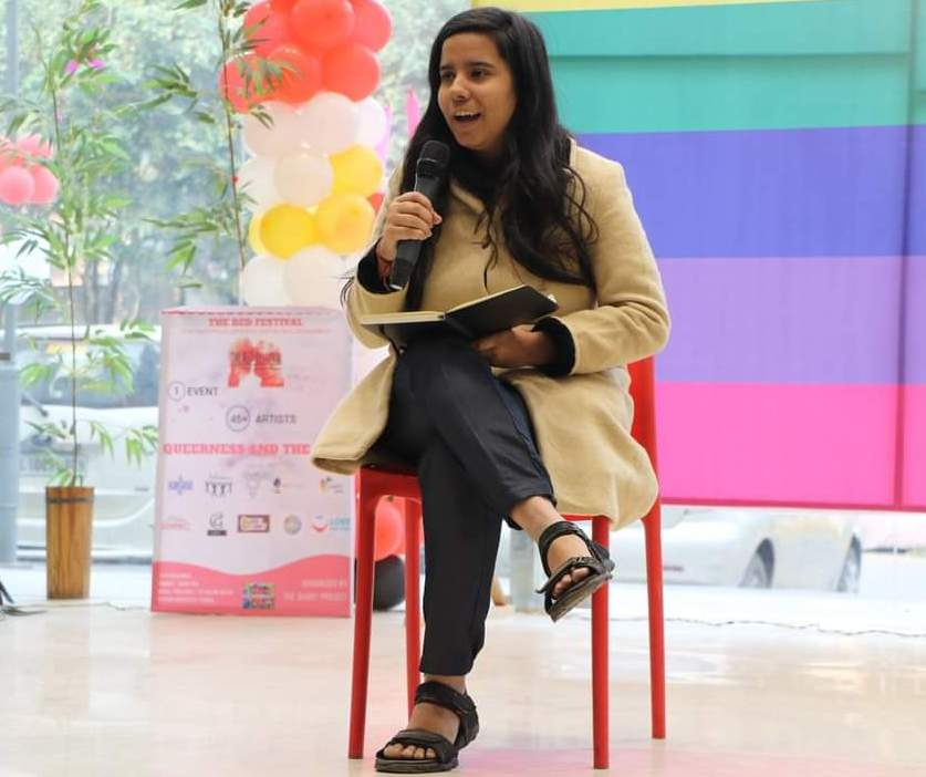 This photograph is a daytime mid-shot that shows the author Meghna Mehra seated on a stage for a book reading session during a queer art event in Delhi. She has a book open on her lap, held with her left hand, and a microphone in her right hand. She smiles as she speaks looking at the audience, which is not visible in the photograph. The backdrop includes a rainbow pride flag; red, white and yellow balloons; a standee flex banner for the event; and a couple of tall house plants – all placed against a glass wall. Some more greenery and cars can be seen parked beyond the glass wall, outside the event venue. The event in question is 'The QUART Project – Red Festival 2.0' held in 2018. Photo courtesy The QUART Project